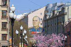 The pedestrian Arbat street in Moscow on a spring day. Arbat street is a portrait of Marshal Zhukov on the wall of a building Stock Image