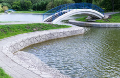 Pedestrian arch bridge. With blue railing above pond is in park Stock Image