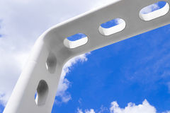 Pedestrian arch bridge. Fragment of apertured white arch of modern pedestrian bridge against background of sky with clouds Royalty Free Stock Photo