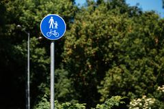 Pedestrian bicycle zone in blue circle on background of green tr. Ees in park. city street sign concept. sign with person and child and bicycle in white and blue royalty free stock image
