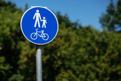 Pedestrian bicycle zone sign in blue circle on background of green trees in park. city street sign concept. sign with person and. Child and bicycle in white and royalty free stock photography