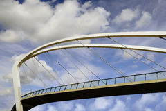 Pedestrian bridge against the blue sky. Pedestrian bridge against the sky with clouds Royalty Free Stock Images