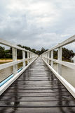 Pedestrian bridge crossing on an overcast and drizzly day. White timber pedestrian bridge crossing on an overcast and drizzly day - no people Royalty Free Stock Photo