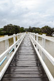 Pedestrian bridge crossing on an overcast and drizzly day. White timber pedestrian bridge crossing on an overcast and drizzly day - no people Royalty Free Stock Image
