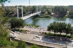 Pedestrian bridge and the embankment of the Ural River. Orenburg, Russia Royalty Free Stock Photo