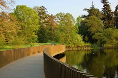 Pedestrian bridge through the lake in spring park. Stock Image