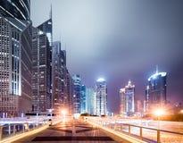 Pedestrian bridge and modern buildings at night Stock Photo
