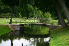 Pedestrian bridge in park. Small pedestrian bridge crossing a stream in a public park Stock Image