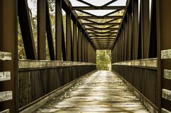Pedestrian bridge. With safety railings built with strong steel girders and  with the walkway made from wooden planking Royalty Free Stock Photo