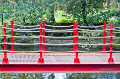 Pedestrian bridge with red ropes and railing Stock Photo