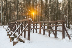 Pedestrian bridge on a snowy park at sunset Royalty Free Stock Image