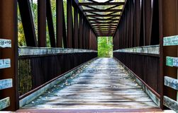 Pedestrian bridge. Strong pedestrian bridge with safety railings made with strong metal girders and the walking part (platform) from wooden planking, background Stock Photos