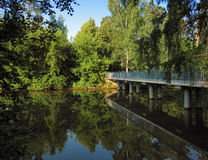 Pedestrian bridge and trees reflecting in the lake Royalty Free Stock Images