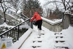 Pedestrian climbs the snow stairs Royalty Free Stock Photos