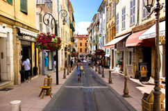 Pedestrian and commercial street in Antibes. Pedestrian street at the commercial center of Antibes with people and a woman walking with bags Royalty Free Stock Images