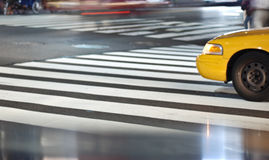 Pedestrian crossing. White piano painted pedestrian crossing on the road and the front of a yellow cab Stock Photos