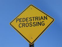Pedestrian Crossing. Yellow pedestrian crossing sign against blue sky Royalty Free Stock Images