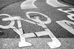 Pedestrian crossing across curved bicycle asphalt line, high contrast photo. Black and white, bicycle symbol stock image