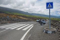 Pedestrian crossing of the asphalt road over volcanic lava in Sainte-Rose De La Reunion, France. Stock Photos