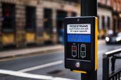 Pedestrian Crossing button in Leeds City Centre that says WAIT for people to cross the road royalty free stock photography