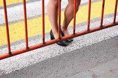 The pedestrian crossing is closed. Women`s feet are on the crosswalk in front of the fence royalty free stock photography