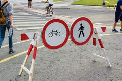 Pedestrian crossing with forbidden crossing signs for pedestrians and cyclists. With pedestrians walking around it stock image
