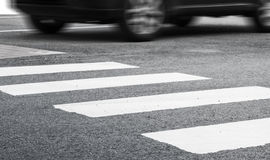 Pedestrian crossing marking and fast moving car. Pedestrian crossing road marking and fast moving car, photo with selective focus and shallow DOF royalty free stock photography