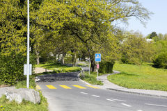 Pedestrian crossing on a narrow and winding road. Pedestrian crossing painted yellow on a narrow and winding road along which a lush trees grows. It is visible stock photo