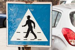 Pedestrian crossing. Old square blue and white road sign. With schematic walking man in hat Stock Image