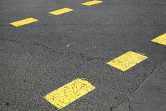 Pedestrian crossing road marking with yellow striped lines Stock Photography