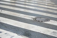 Pedestrian Crossing and Sewage Manhole Cover Stock Photography