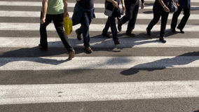 Pedestrian Crossing and shadows. Taken on a Pedestrian crossing in Rome with a line of monotone legs and on the far left a man in green with a yellow bag stock photography