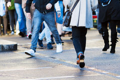 Pedestrian crossing the street. They are unrecognizable because the heads are not shown Royalty Free Stock Images