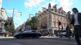 Pedestrian crossing, traffic, taxis and red double decker London buses in Oxford Street, London, Englan stock footage