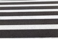 Pedestrian crossing. White markings on a black asphalt road from a pedestrian crossing. photo closeup in rainy cloudy weather Royalty Free Stock Photo