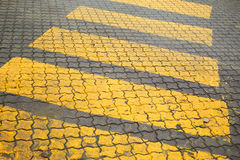 Pedestrian crossing, yellow marking on road pavement. Pedestrian crossing, yellow marking on cobblestone road pavement Royalty Free Stock Images