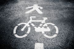 Pedestrian and cycle lane symbol on asphalt. Royalty Free Stock Images