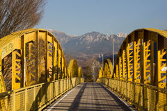 Pedestrian and cycle  yellow steel bridge with mountains in the Royalty Free Stock Photo