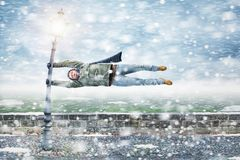 Pedestrian gets blown away in a snowstorm. Funny image of a pedestrian getting blown away in a blizzard. He manages to hold on to a street lamp while floating Stock Photography