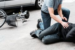 Pedestrian helping accident victim. Pedestrian helping a victim of an automobile accident lying on the street next to a broken bike stock image