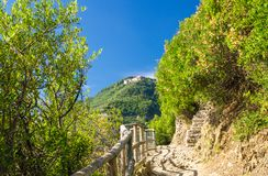 Pedestrian hiking stone path trail with railing between Corniglia and Vernazza villages with green trees, blue sky background, Nat. Ional park Cinque Terre, La royalty free stock photo