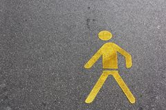 Pedestrian lane sign yellow on the asphalt ground. Pedestrian lane sign in yellow on the asphalt ground Royalty Free Stock Image