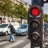 Pedestrian lights. With blurred city traffic in the background at the Champs Elysees in Paris, France Stock Images