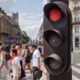 Pedestrian lights in Paris, France. Pedestrian lights with blurred people in the background crossing a street in Paris, France Royalty Free Stock Photo