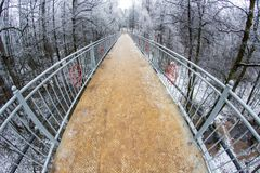 Pedestrian metal bridge across the ravine with the river. Repinka in winter. Obninsk, Russia stock photos
