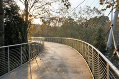 Pedestrian path bridge bending into the sunlight stock photography