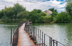 Pedestrian pontoon-bridge over small river Schemylivka in outskirts of Dnipro city, Ukraine Royalty Free Stock Images