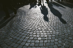 Pedestrian shadows on cobblestone pavement Royalty Free Stock Image