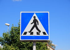 Pedestrian sign with blue sky and tree background Stock Photos