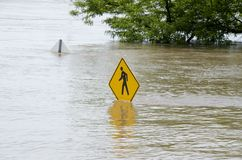 Flooding. A pedestrian sign in water during a major flood (angle 2 Royalty Free Stock Images